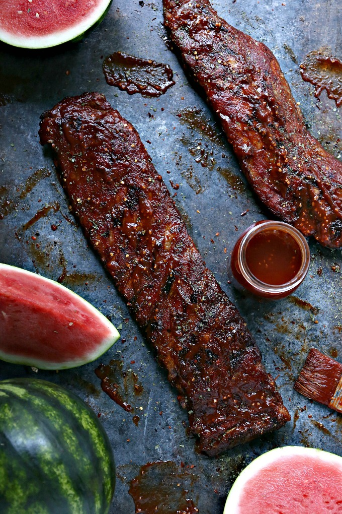 Grilled Slabs of Ribs coated with Watermelon BBQ Sauce pictured with whole watermelons, cut watermelons and a mason jar filled with bbq sauce.