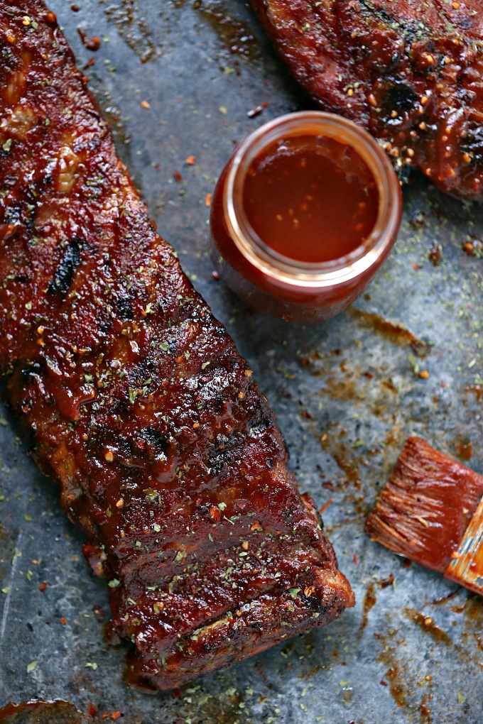 Grilled Ribs brushed with Watermelon BBQ Sauce with a jar of sauce nearby.