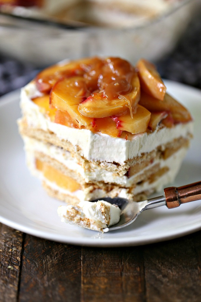 Slice of Peach Icebox Cake with Easy Caramel Sauce served on a plate with a copper spoon.