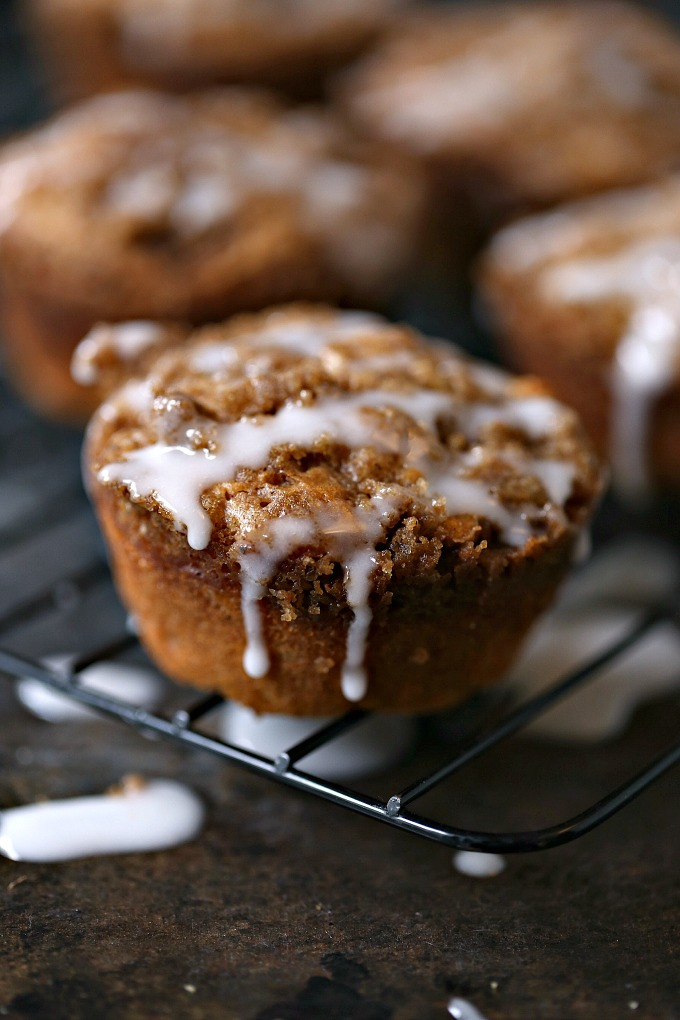 Cookie Butter Apple Cinnamon Muffins covered with Streusel Topping on a cooling rack being drizzled with icing!