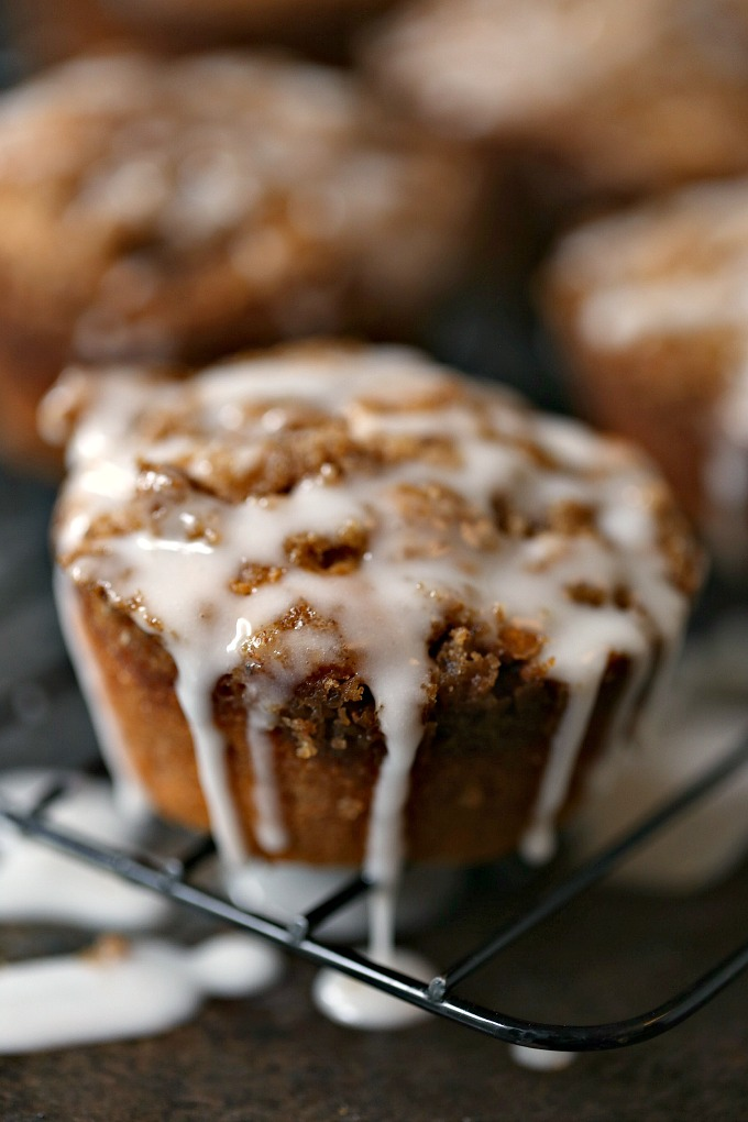 Cookie Butter Apple Cinnamon Muffins covered with Streusel Topping on a cooling rack being drizzled with icing, icing and more icing!