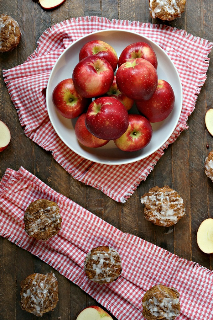 Cookie Butter Apple Cinnamon Muffins covered with Streusel Topping on a tabletop with SweeTango apples in a bowl!