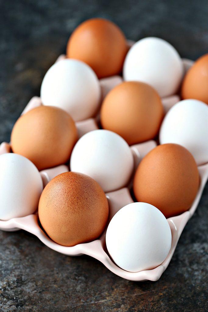 Farm Fresh Eggs in a pink ceramic egg carton on a dark counter.