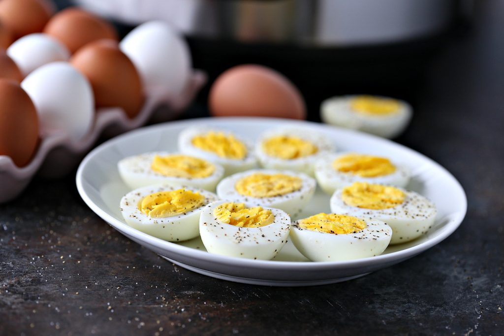 Cooked hard boiled eggs on a white plate with eggs and an instant pot in the background.