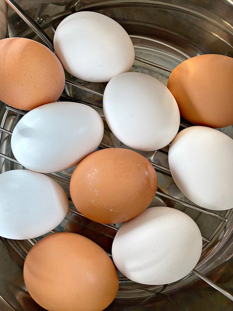 Brown eggs and white eggs inside an instant being prepped to cook.