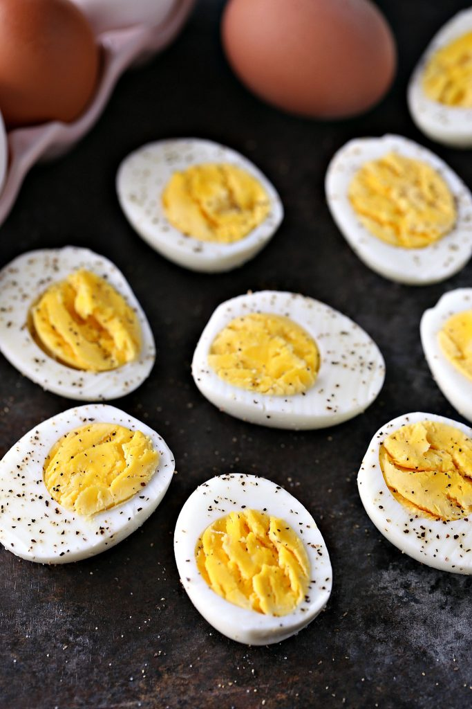 Instant pot hard boiled eggs cut in half, sprinkled with salt and pepper. In the background you can see a pink egg ceramic egg carton with an egg in and an egg beside it on a dark surface.