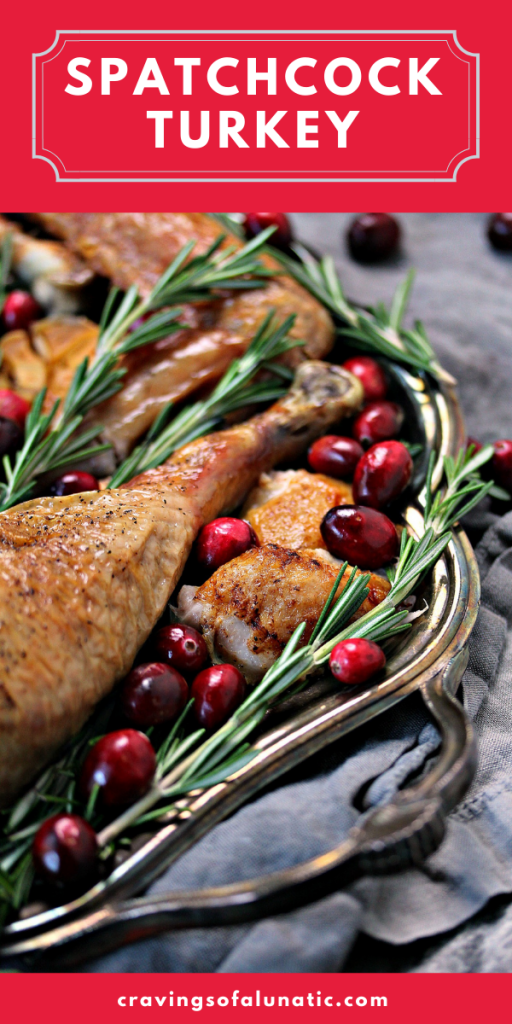 How to Cook a Spatchcocked Turkey served on silver platter with herbs and cranberries scattered about.