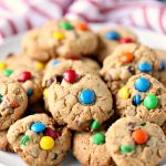 monster cookies piled on a white plate with a red and white cloth napkin in the backgroun