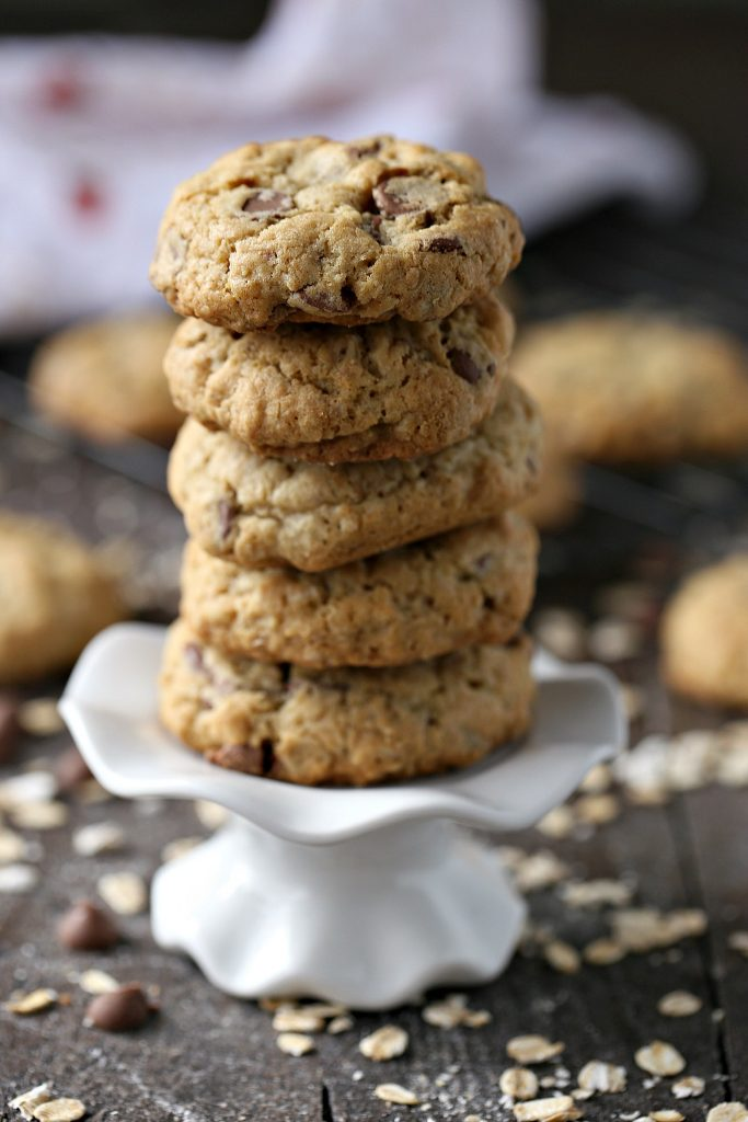 Oatmeal Chocolate Chip Cookies stacked on a white mini cake stand.