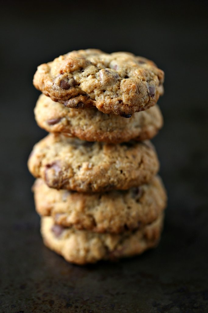 Oatmeal Chocolate Chip Cookies stacked high on a dark surface.