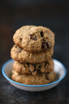 Oatmeal Raisin Cookies stacked on a tiny white and blue plate.
