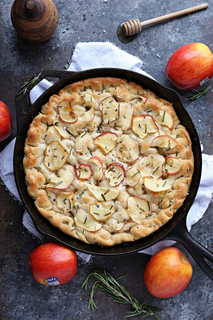 overhead image of apple rosemary focaccia bread recipe in a cast iron pan on a white napkin. Apples, fresh rosemary and honey are pictured as well.