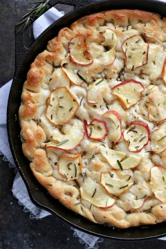 overhead image of apple rosemary focaccia in a black cast iron pan on a white napkin