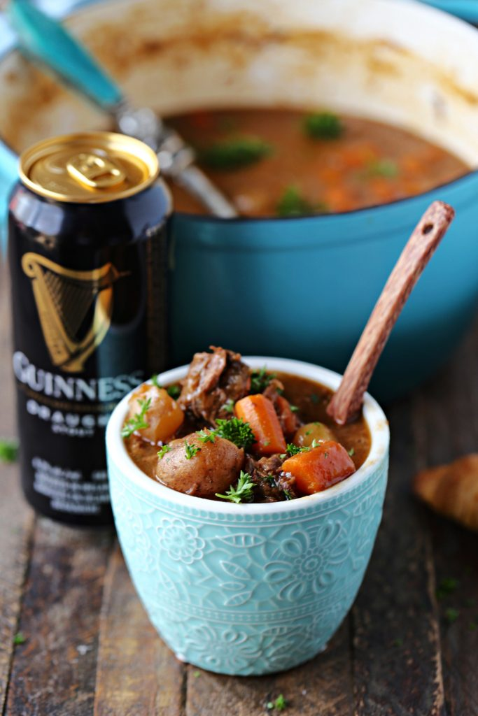 Guinness Beef Stew served in a blue bowl with a wooden spoon in in, Guinness beer and a dutch oven filled with stew are in the background.