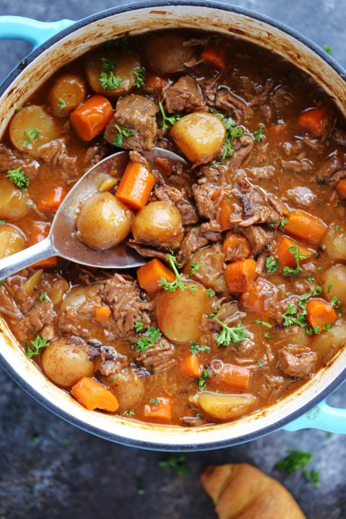 Guinness Beef Stew in a blue dutch oven with a spoonful being lifted out by a blue and silver spoon