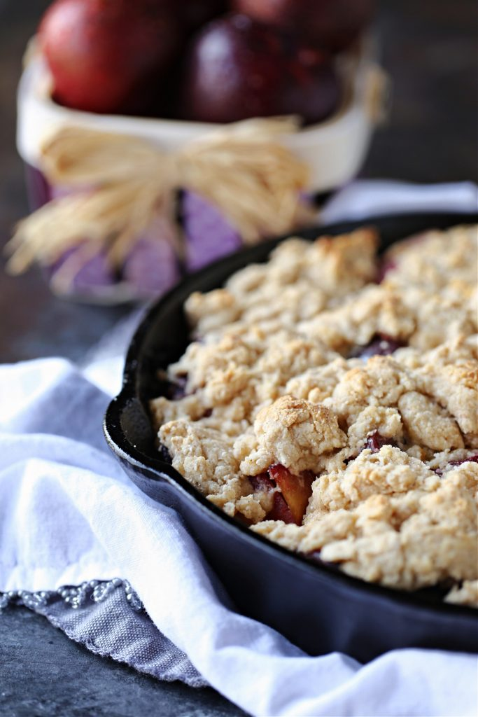 Plum Cobbler in a cast iron skillet with a basket of plums in the background