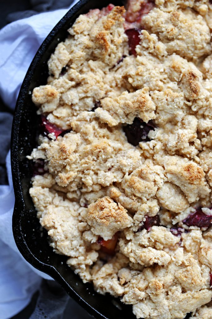 Plum Cobbler baked in a cast iron skillet.